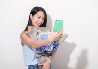 Woman holding bouquet of flower and taking selfie with mobile phone