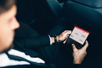 Businessman sitting in car scheduling meetings on smartphone