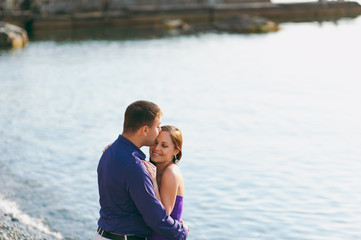 A loving couple in purple outfits on the seashore