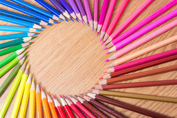Many multicolored pencils on a wooden background. Round frame of different colored pencils with space for text. Copyspace. Back to school.