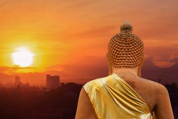 buddha statue on sunset sky and city blur background beautiful