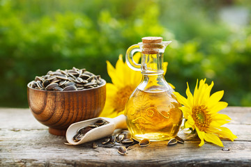 Spoed Foto op Canvas Kruiderij Organic sunflower oil in a small glass jar with sunflower seeds and fresh flowers. Outdoors