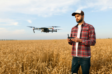 Compact drone hovers in front of farmer with remote controller in his hands. Quadcopter flies near pilot. Agronomist taking aerial photos and videos in a wheat field