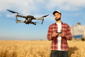 Compact drone hovers in front of farmer with remote controller in his hands. Quadcopter flies near pilot. Agronomist taking aerial photos and videos in a wheat field Wall mural