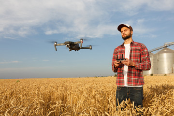 Drone hovers in front of farmer with remote controller in hands near grain elevator. Quadcopter flies near pilot. Agronomist taking aerial photos and videos in a wheat field.