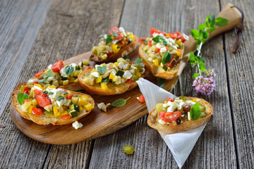 Warmes Fingerfood: Leckere Crostini mit Feta-Grillgemüse und Olivenöl - Warm canapes: Baked crostini with mixed  Greek  vegetables with feta cheese served on a wooden cutting board