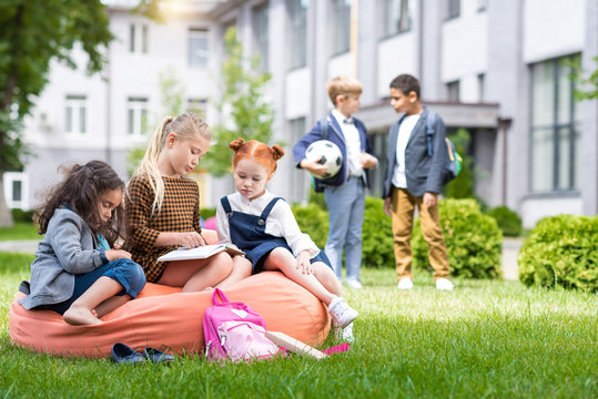 adorable multiethnic schoolgirls sitting on bean bag chair and reading book while schoolboys standing with soccer ball on schoolyard
