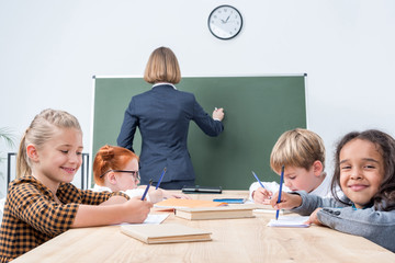 back view of teacher writing on chalkboard while students studying in classroom