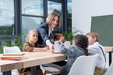 young female teacher working with cute little schoolchildren in classroom