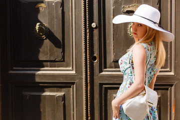 Young traveling girl: standing near an old door. Vacation, summer, holiday, journey, concept.