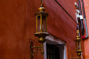 Street lamp on a red wall background. Wall with street lamp.