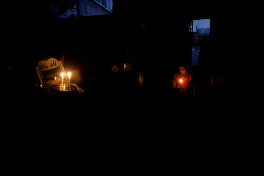 Palestinian girl holds a candle to light up her family's house during power cut in Beit Lahiya town in the northern Gaza Strip