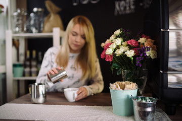 The girl adds cinnamon to the cup with coffee in cafe. Young woman barista working in coffee shop. Soft focus on flowers