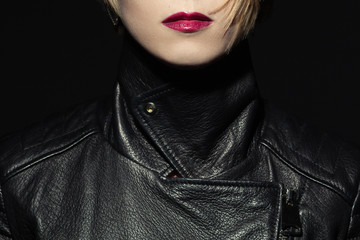 Tough girl and femme fatale concept. Rock star style. Close up portrait of young woman wearing expensive luxurious black leather jacket. Studio shot