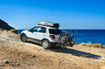 Car with roofbox and bicycle on the road