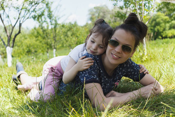 Woman and a little girl lies on the green grass in the garden