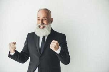 successful senior businessman celebrating victory, raising fists on white background