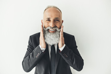 happy senior businessman touching his beard and smiling at camera