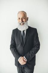 handsome stylish senior businessman leaning back on white wall