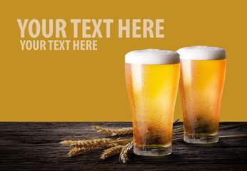 Cold beer with wheat on wooden table. Glasses of light beer on the yellow background with copy space.
