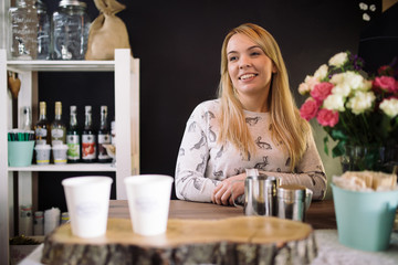 Young woman barista working in coffee shop. Smiling girl at the bar in the cafe