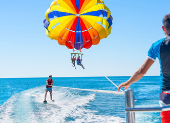 Happy couple Parasailing in Dominicana beach in summer. Couple under parachute hanging mid air. Positive human emotions, feelings, family. Young man glides on water skiing on the waves.