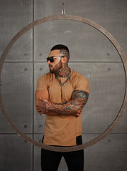 Sexy closeup portrait of Elegant handsome male model with fashion tattoo and a black beard standing and posing for model tests or to journal in trend fashionable clothes. Professional Studio image