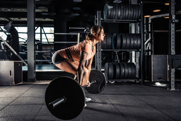 Woman doing heavy  deadlift exercise in gym
