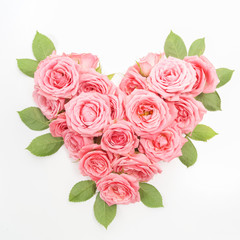 Heart shaped bouquet of roses on white background. Top view