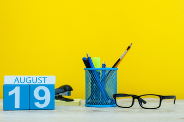 August 19th. Image of august 19, calendar on yellow background with office supplies. Summer time