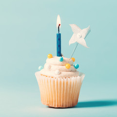 Cupcake with candle celebration theme on a blue background