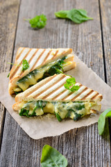 Im Kontaktgrill gepresstes italienisches Panini mit jungem Blattspinat, Zwiebeln  und Käse - Pressed and toasted double panini with spinach, onions and cheese served on sandwich paper