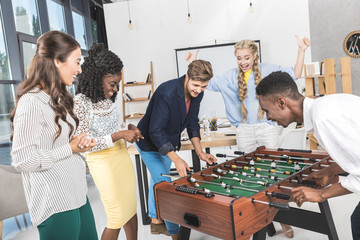businesswomen watching multicultural colleagues playing table football in office