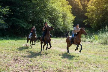 Group of friends riding horses on the river