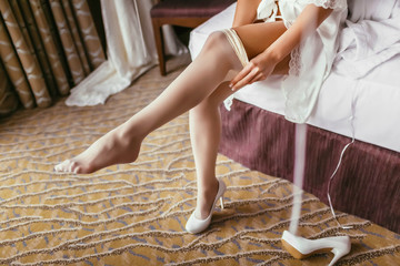 Bride in a silk robe with beautiful slim legs is putting on stockings. Wedding morning preparation. Dressing lingerie, boudoir.