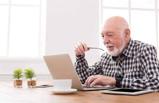 Smiling senior man using laptop copy space