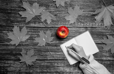 Female hand writing something in notebook next to apple