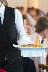 Waitress serving dinner at a feast