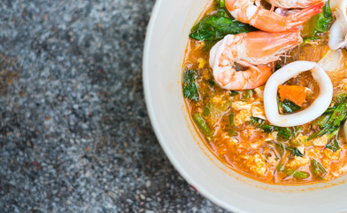 Close up Sukiyaki (Thai Suki) in broth Mixed sea food with vermicelli and vegetables. Copy space for design element.