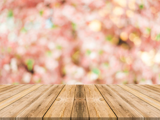 Wood table top on blurred background of pink cherry blossom flower - can used for display or montage your products