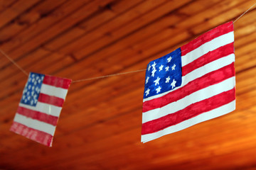 American flag hanging on threads against the background of wooden ceiling painted on paper