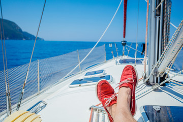 A pair of man legs in topsiders on white yacht deck. Yachting