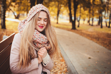 portrait of young beautiful woman walking in stylish warm outfit in sunny autumn day in park, wearing pink coat and knitted snood. Casual lifestyle in the city