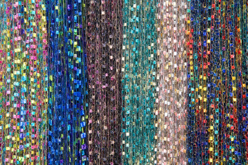 Background fabric strings creating scarfs, multiple colored scarves hanging in rows.. Blue, green, brown, rainbow pink, yellow. Hanging vertically