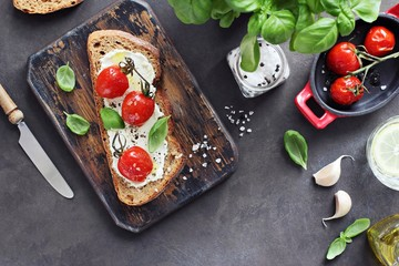 Sandwich with oven baked tomatoes, cream cheese and basil. Rye bread with grilled tomatoes and ricotta cheese. Overhead view