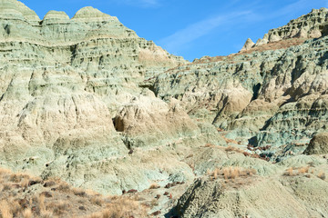 Surrealistic landscape in John Day Fossil Beds National Monument Blue Basin area with grey-blue badlands. A branched ravine and Heavily eroded formations.