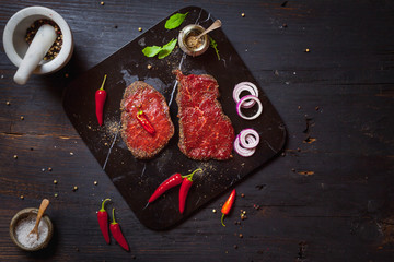 Raw ribeye beef steak on black marble deck on an old rustic table. Top view