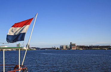 Harbour view of Amsterdam with a flag of the Netherlands