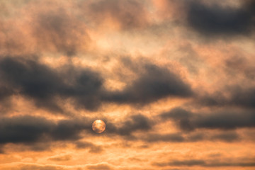orange sky with smoky clouds at sunset moving over the sun