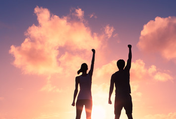 People, power, and victory.  Silhouette of confident man and woman with fist in the air.